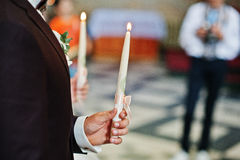 Groom with bride holding burning candles at hand on wedding chur. Ch ceremony Royalty Free Stock Photography