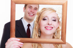 Groom and bride holding empty frame Stock Photography