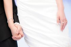 Groom and Bride holding hands with rings on their fingers stock photo