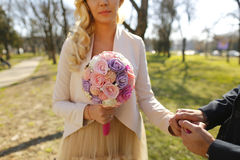 Groom and bride holding hands and wedding bouquet Stock Photography