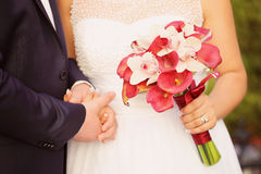 Groom and bride holding hands and wedding bouquet Royalty Free Stock Photo