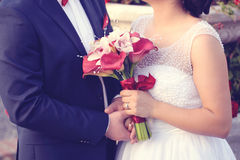 Groom and bride holding hands and wedding bouquet Royalty Free Stock Image