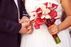 Groom and bride holding hands and wedding bouquet Royalty Free Stock Images