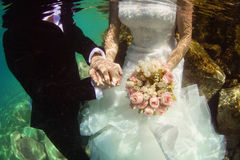 Groom and bride holding hands and wedding bouquet underwater Royalty Free Stock Photography