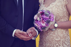 Groom and bride holding hands Stock Photography