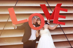 Groom and bride holding LOVE letters Stock Photography