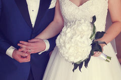 Groom and bride holding wedding bouquet Royalty Free Stock Image