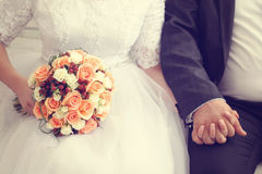 Groom and bride holding wedding bouquet Royalty Free Stock Photography