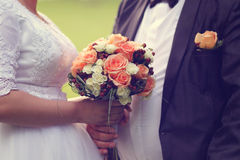 Groom and bride holding wedding bouquet Stock Photos