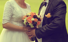 Groom and bride holding wedding bouquet Stock Photography