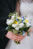 Groom  and bride holding a wedding bouquet in a park, close-up, Royalty Free Stock Photography