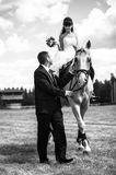 Groom with bride on horse Royalty Free Stock Photos
