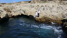 Groom bride jump off a cliff into the ocean stock video footage