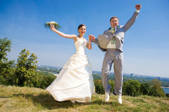 Groom and bride jumping Stock Image