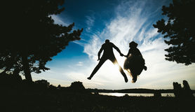 Groom and bride jumping against the beautiful sky Stock Photos