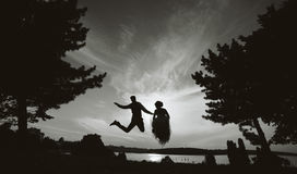 Groom and bride jumping against the beautiful sky Royalty Free Stock Photography