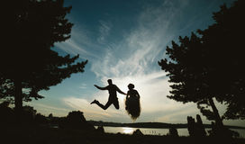 Groom and bride jumping against the beautiful sky Royalty Free Stock Images