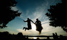 Groom and bride jumping against the beautiful sky Royalty Free Stock Image