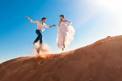 Groom and bride jumping Stock Photos