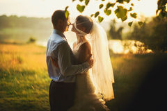 Groom and bride is kissing on the background lake and forest Stock Photo