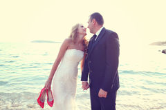 Groom and bride kissing  on the beach on a sunny day Royalty Free Stock Photography