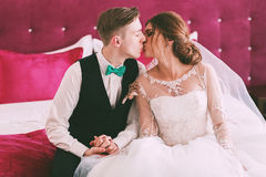 Groom and bride kissing on bed Royalty Free Stock Photos