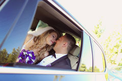 Groom and bride kissing in the car Stock Image