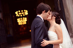 Groom and bride kissing in front of the church Royalty Free Stock Photos