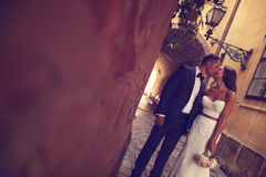 Groom and bride kissing. Groom kissing his bride in the city Stock Images