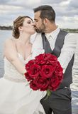 Bride and room with bouquet of red roses Royalty Free Stock Photo