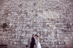 Groom and bride kissing near brick wall Royalty Free Stock Image