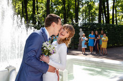 Groom and bride kissing near a fountain Royalty Free Stock Photo