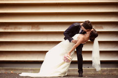 Groom and bride kissing near a stripped wall Royalty Free Stock Images