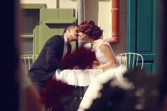 Groom and bride kissing in a openair restaurant Royalty Free Stock Photos