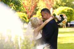 Groom and bride kissing in the park Stock Photo