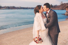 Groom and bride kissing on river bank Stock Photo