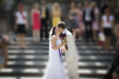 Groom and bride kissing on stairs of palace Stock Photo