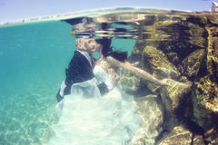 Groom and bride kissing underwater Royalty Free Stock Images