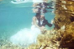 Groom and bride kissing underwater Stock Image