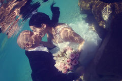Groom and bride kissing underwater Stock Photos