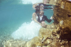 Groom and bride kissing underwater Royalty Free Stock Photos