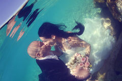 Groom and bride kissing underwater Royalty Free Stock Photography