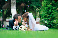 Groom and bride lie on a grass around soap bubbles Royalty Free Stock Photos