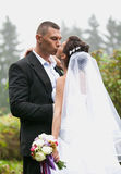 Groom and bride with long veil kissing at park Royalty Free Stock Photo