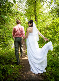 Groom and bride in long white dress walking at forest Royalty Free Stock Photography