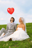 Groom and bride looking at red balloon stock photos