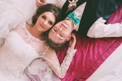 Groom and bride lying on bed Royalty Free Stock Images