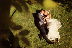 Groom and bride lying on grass Royalty Free Stock Photo