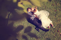 Groom and bride lying on grass Stock Images