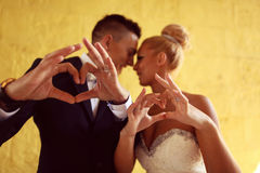 Groom and bride making love sign with their hands Stock Photography
